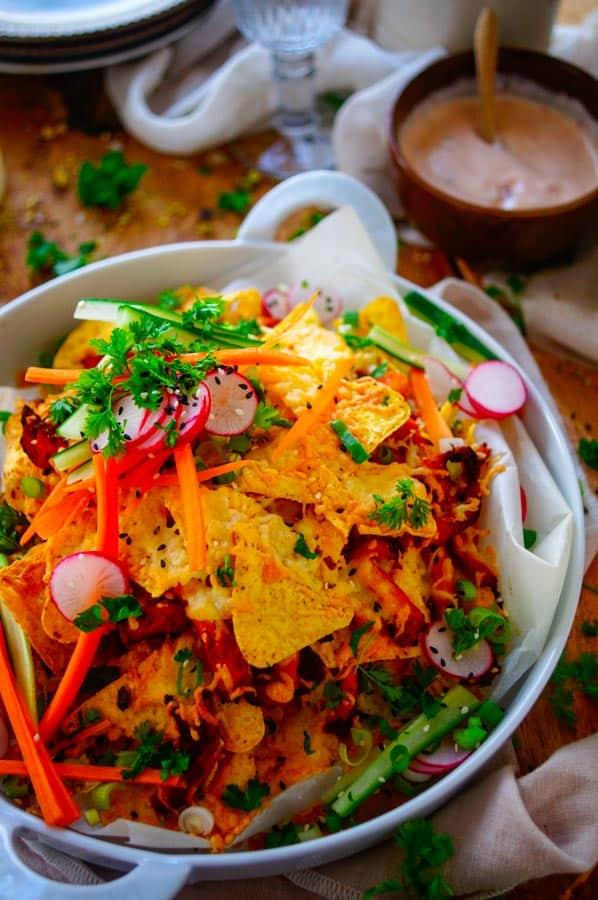 Loaded nacho's. Deze loaded nacho's zijn een origineel simpel hapje voor tijdens een zomerse borrel of als starter bij een barbecue. In deze lekkere eenvoudige nachoschotel vind je de typishe maïstortilla's, reepjes varkenshaasje, snelle gepekelde groentjes en een romige chili dip