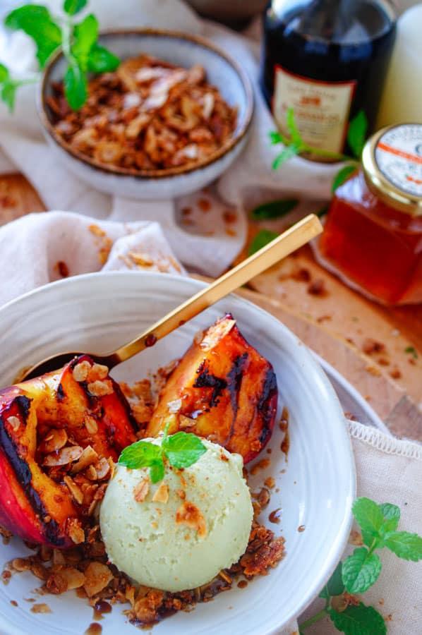 Pistache-ijs met gegrilde perziken. Heerlijk homemade pistache-ijs geserveerd met zomerse gegrilde perziken en een olijfolie crumble. Het ideale makkelijke dessertje als afsluiter van een barbecue.