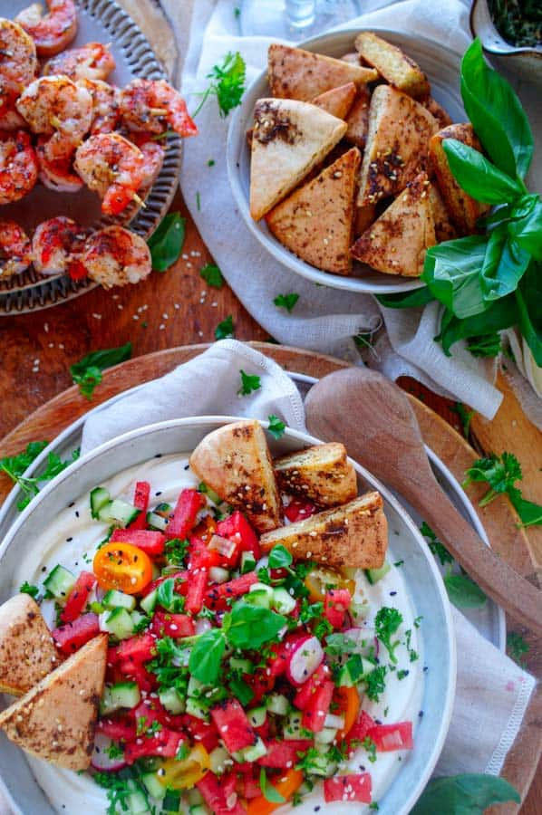 Watermeloen salade met opgeklopte feta. Een frisse zomerse salade op basis van watermeloen, komkommer en radijsjes geserveerd met romig opgeklopte feta. Een origineel en snel te maken bijgerecht voor bij een barbecue of als hapje met za'atar pita chips