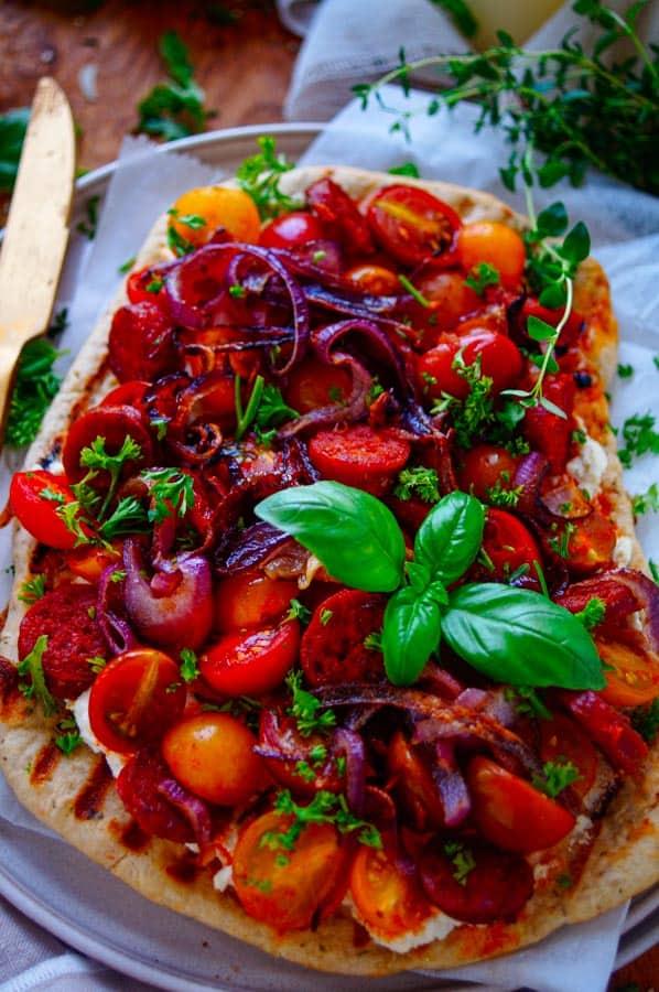Platbrood pizza met chorizo, tomaten en ricotta. Een lekker makkelijk recept voor Platbrood pizza met chorizo, tomaten en ricotta. Een eenvoudige pizza ideaal als doordeweekse maaltijd of als hapje voor bij de borrel.